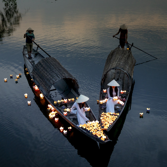 """""""Two Vietnamese girls with wihte tradition Ao Dai are lighting candle in lantern to pray in the river"""" stock image"""
