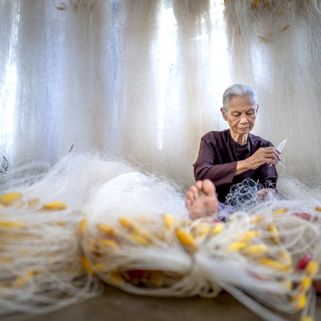 """an elderly woman sitting mending a fishing net"" stock image"