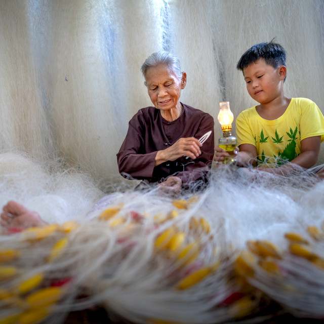 """""""two grandchildren sitting making a fishing net together"""" stock image"""