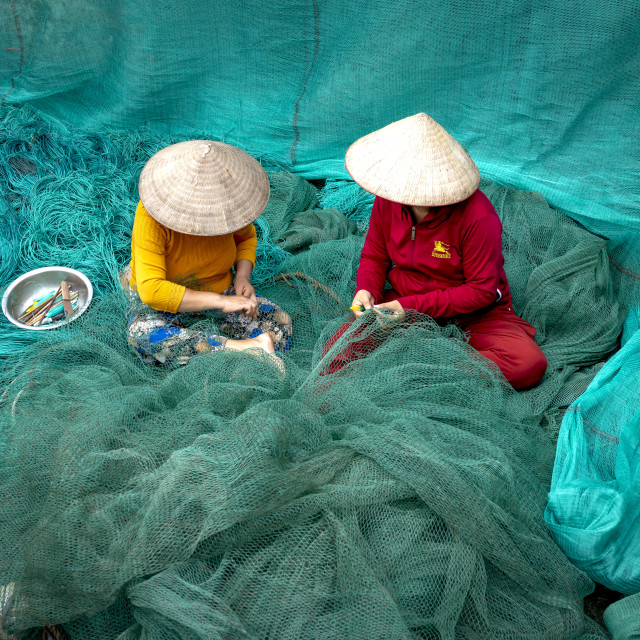 """""""Two unidentified women are mending a fishing net"""" stock image"""