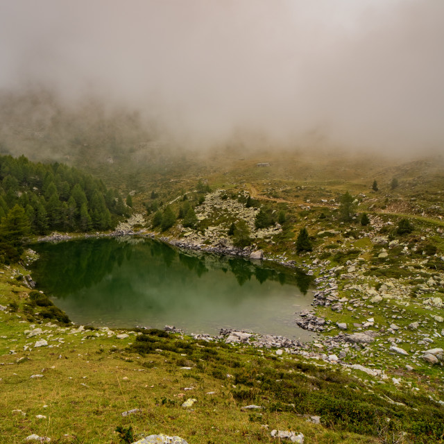 """Mountain pond reflects the surrounding nature shrouded in mornin"" stock image"