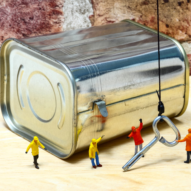 """""""Miniature figure workman using a crane to manoeuver the key for a corned beef tin can opening concept"""" stock image"""