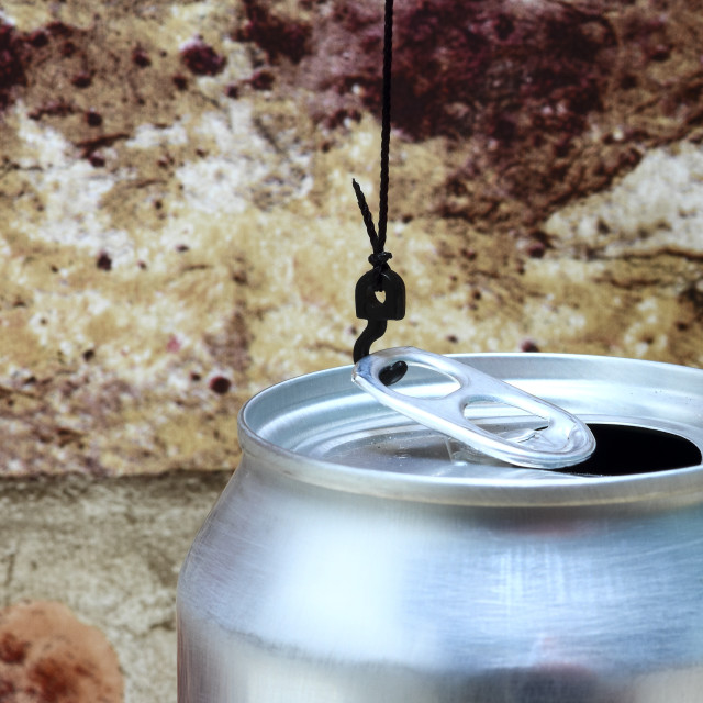 """""""Conceptual image of a cranes hook attatched to the ring pull of an aluminium fizzy drinks can"""" stock image"""