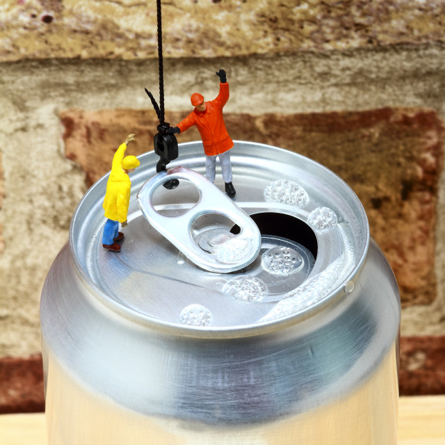"""""""Conceptual image of miniature figure workmen attaching a cranes hook to the ring pull of an aluminium fizzy drinks can"""" stock image"""