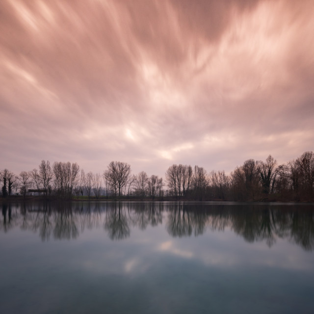 """A red and cloudy sky reflected in the water of a lake at sunset"" stock image"