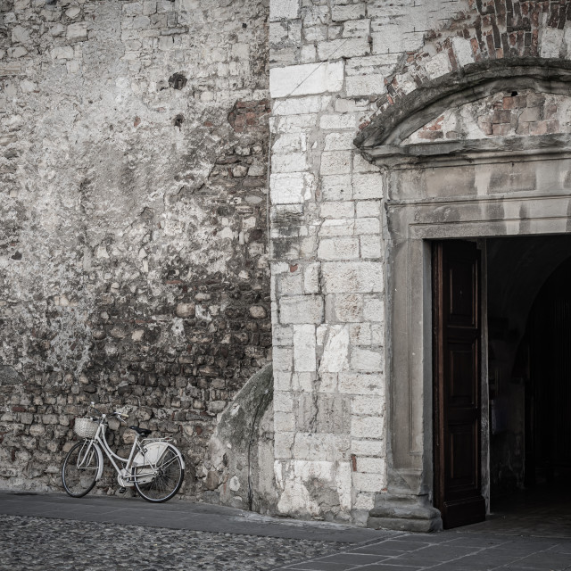 """Bicycle leaning against the brick wall of a church with the door"" stock image"
