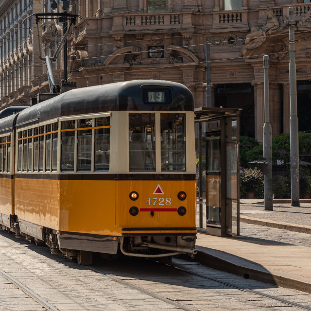 """A yellow tram passes through the streets of the city of Milan"" stock image"