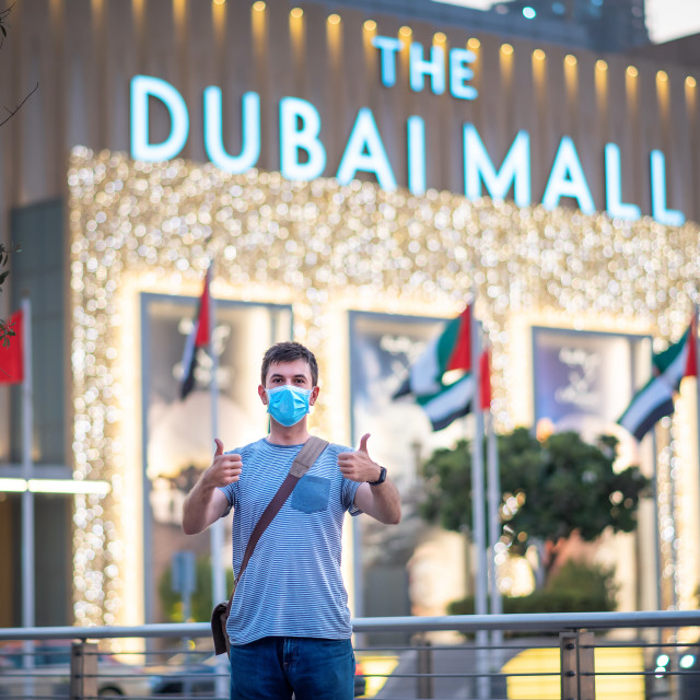 """""""Male tourist wearing surgical face mask in front of the Dubai mall main entrance. New normal for shopping, travel and leisure after the coronavirus, Covid-19 pandemic"""" stock image"""