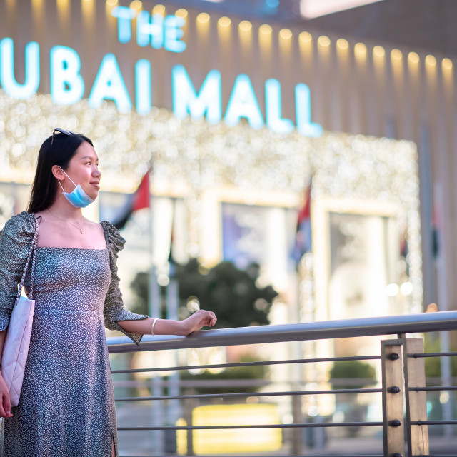 """""""Asian woman wearing surgical face mask in front of the Dubai mall main entrance. New normal for shopping, travel and leisure after the coronavirus, Covid-19 pandemic"""" stock image"""