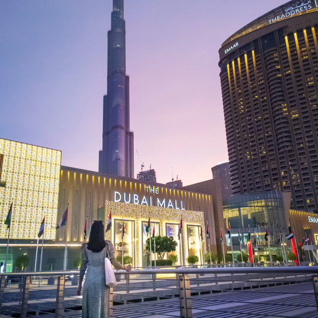 """""""Woman standing in front of the Dubai mall main entrance with Burj Khalifa in rising in the background. Largest shopping mall by area and one of the main attractions in Dubai, UAE"""" stock image"""