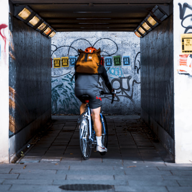 """""""Cyclist going through the Subway, East Road, Cambridge UK."""" stock image"""
