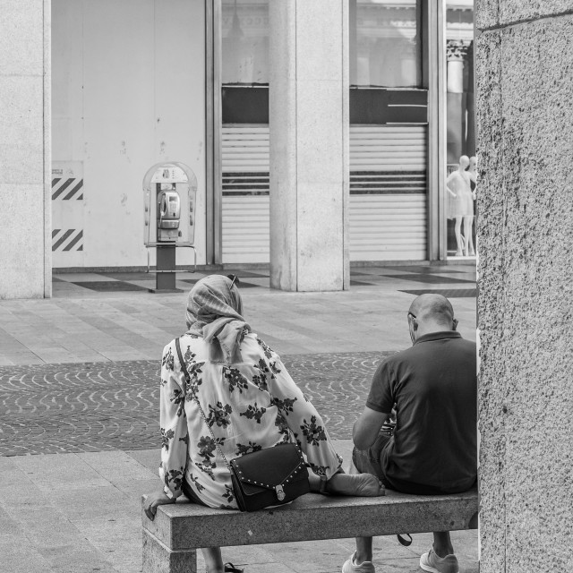 """Two people sitting on a bench shot from behind in a street in th"" stock image"