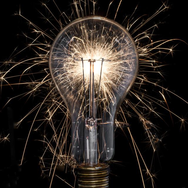 """A vintage lightbulb in a shower of sparks"" stock image"