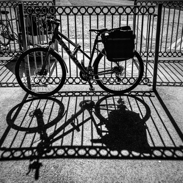 """""""A contre jour image of a bicycle and railings casting dramatic shadows"""" stock image"""