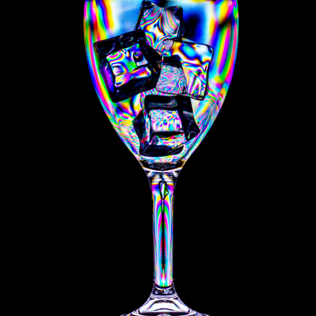 """""""The effect of polarized light on ice in a plastic wineglass"""" stock image"""