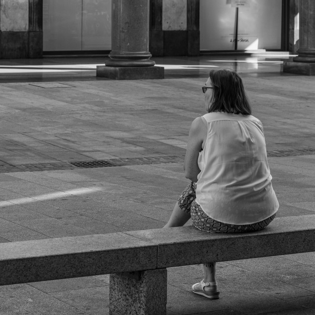 """Woman sitting on a bench shot from behind in a street in the cen"" stock image"