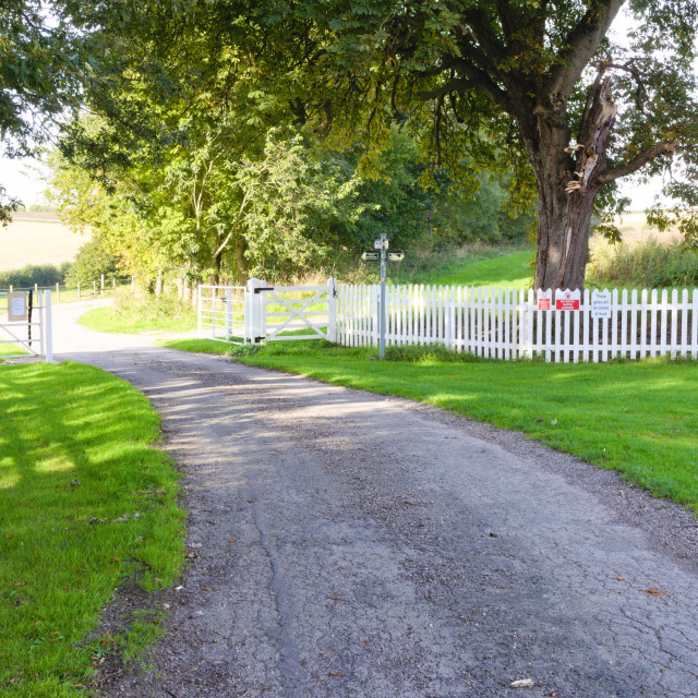 """White picket fence with open gate across a country lane."" stock image"