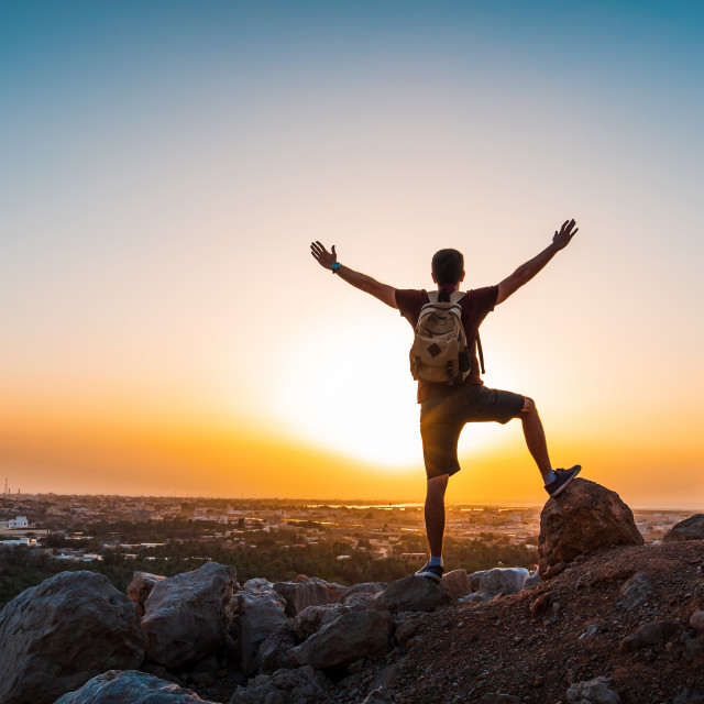 """""""Male hiker celebrating climbing to the top at sunset"""" stock image"""