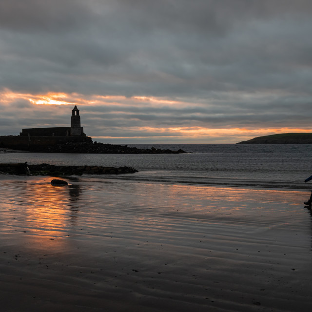 """""""Silhouette of Harbour Light Tower and walker at dusk, Port Lagon, Dumfries & Galloway, Scotland"""" stock image"""