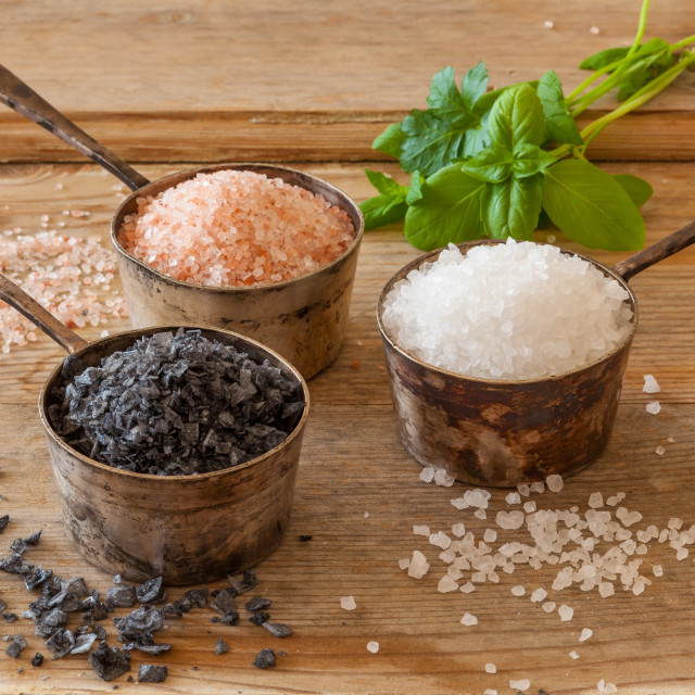 """Three different types of salt in silver containers on a worn out"" stock image"