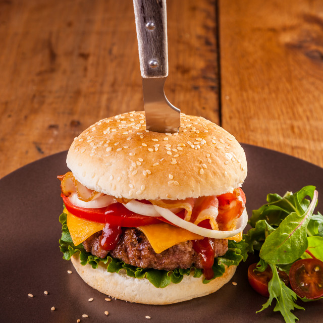 """A delicious juicy hamburger served with a knife stuck in the bun"" stock image"