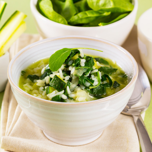 """A bowl with rice, spinach and zucchini, served like a soup."" stock image"