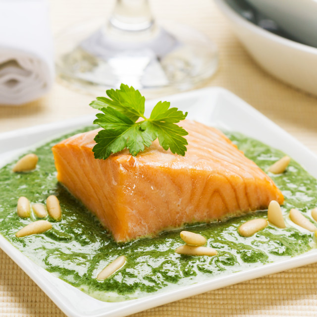 """Steamed salmon in a spinach cream sauce with pine seeds."" stock image"