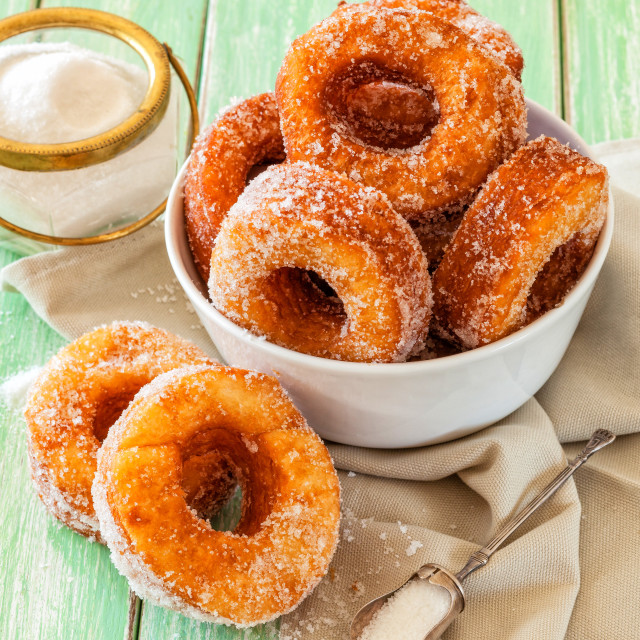 """Homemade sugared cronuts in a bowl on a worn out wooden table"" stock image"