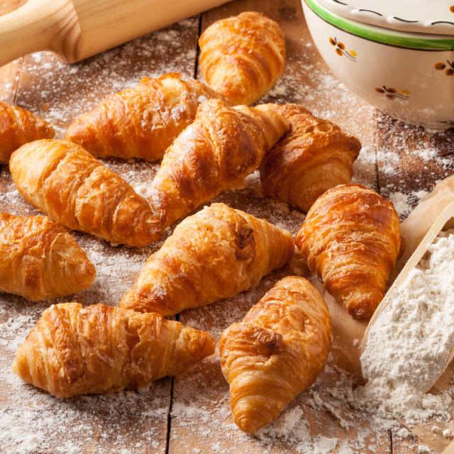 """Homemade mini croissants on a wooden kitchen table."" stock image"