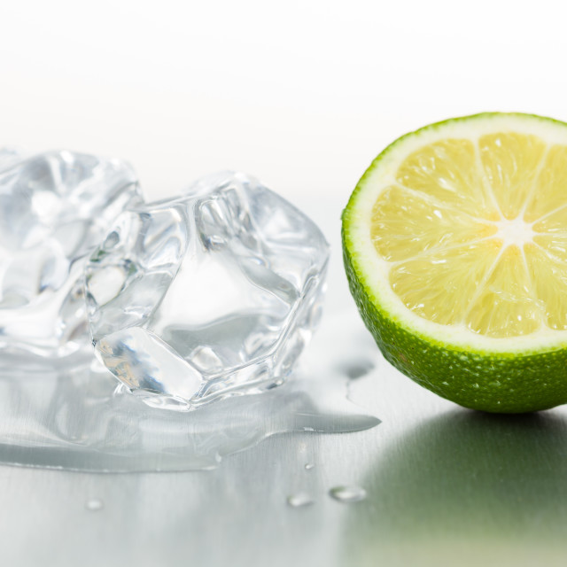 """Half of fresh lime with ice cubes on shiny metal surface"" stock image"