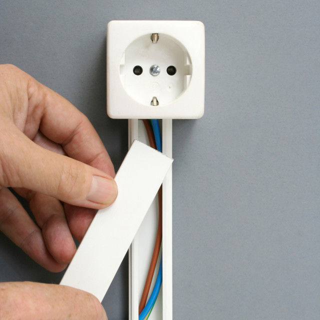 """Installing a power outlet with surface mount electric wiring cha"" stock image"