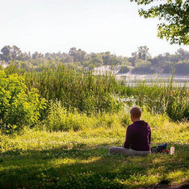 """A woman is meditating, in front of the river in the morning"" stock image"
