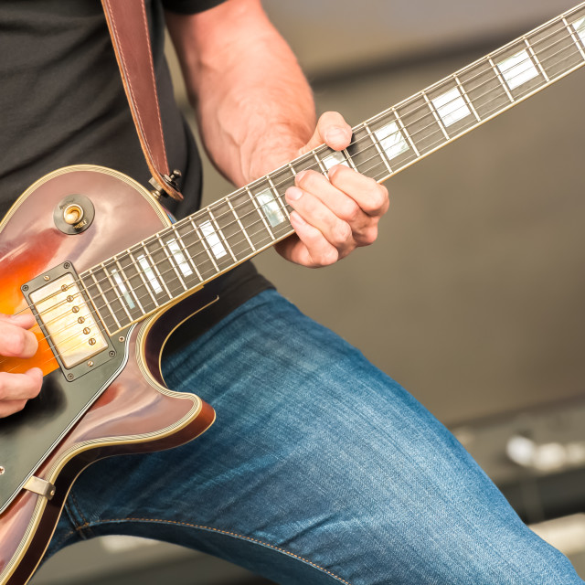 """musician strumming an electric guitar"" stock image"