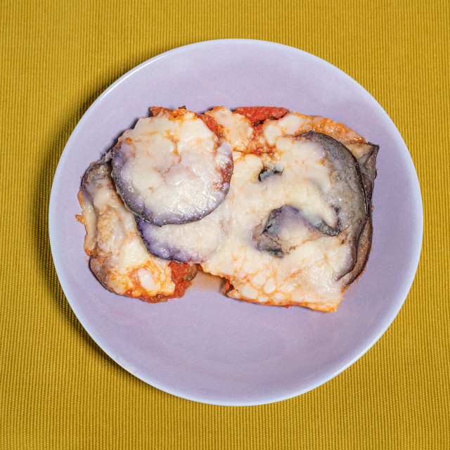 """""""Aubergine parmigiana served in a lilac colored dish placed on a"""" stock image"""