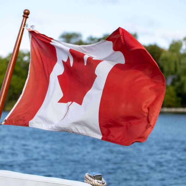 """""""Canadian flag flies on boat's stern"""" stock image"""