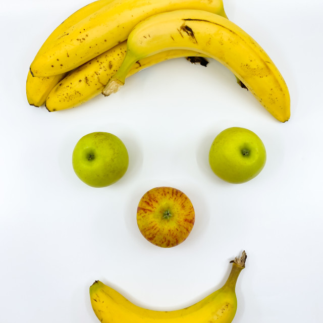 """Fruit in the shape of a face with apples and bananas"" stock image"