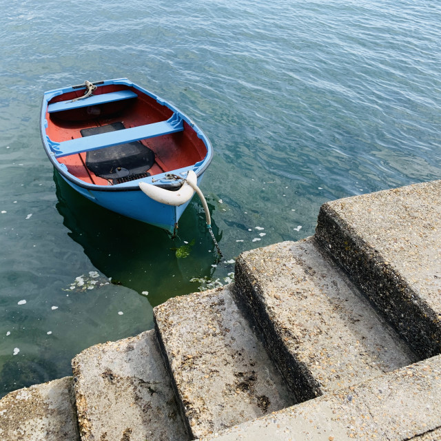 """""""Blue boat tie up at harbour steps"""" stock image"""
