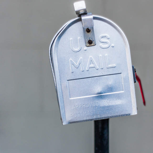 """Metal US Mail style mailbox on fence outside a home"" stock image"