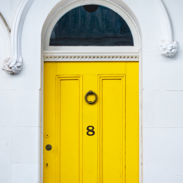 """Bright yellow front door with decorative panels and mouldings"" stock image"