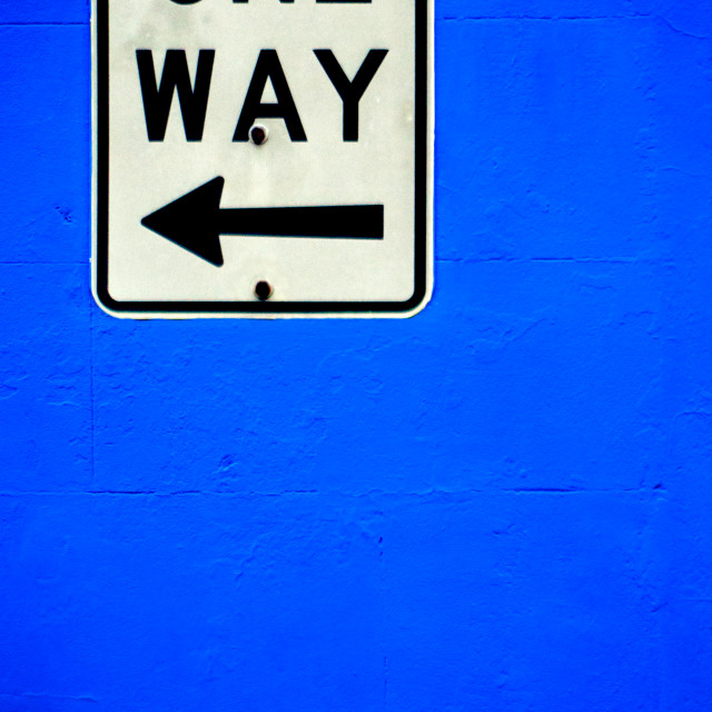 """One Way traffic sign on a bright blue painted wall"" stock image"