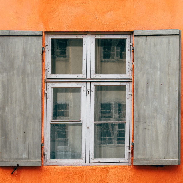 """""""Old wooden window shutters of an european house with orange painted facade"""" stock image"""
