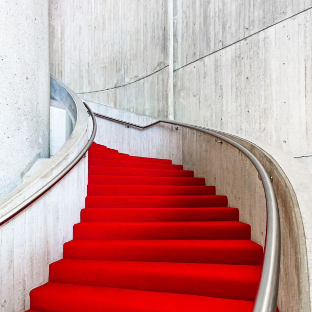 """A bright red carpet winds its way up a curved staircase"" stock image"