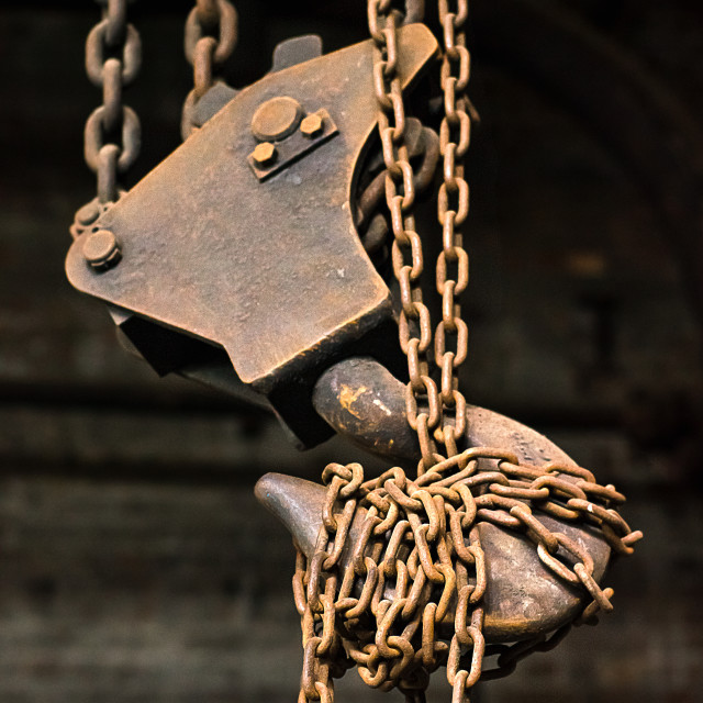 """Rusty industrial hook and chain in an abandoned factory"" stock image"
