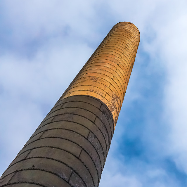 """Angle view of a chimney stack at an abandoned factory against a cloudy blue sky"" stock image"