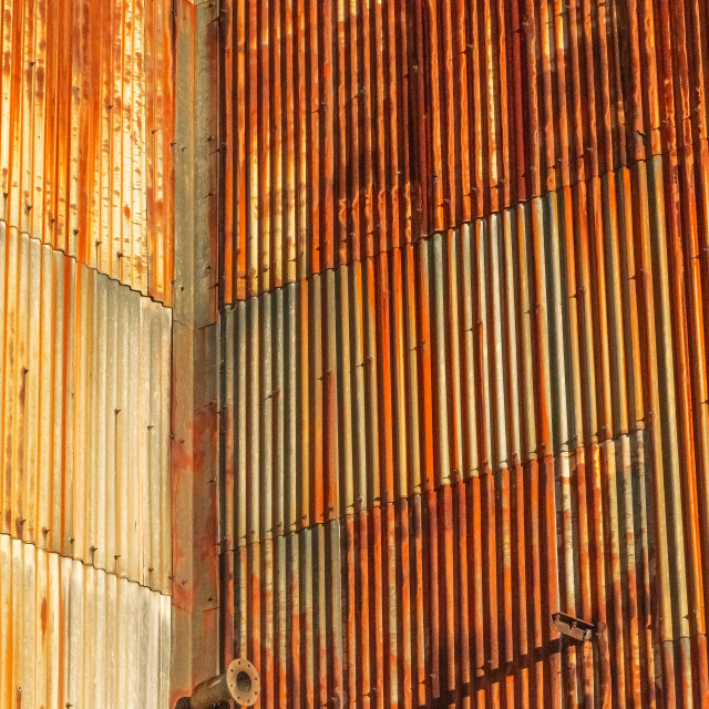 """Rusting corrugated steel wall on the exterior of an abandoned factory"" stock image"