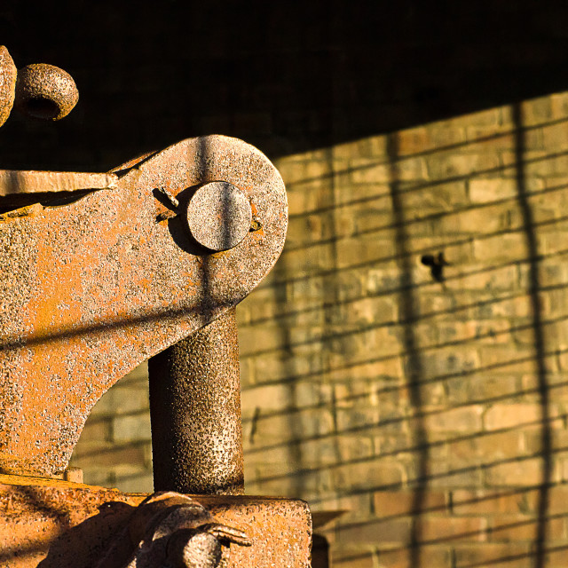 """Rusting metal object in an abandoned factory against a brick wall"" stock image"