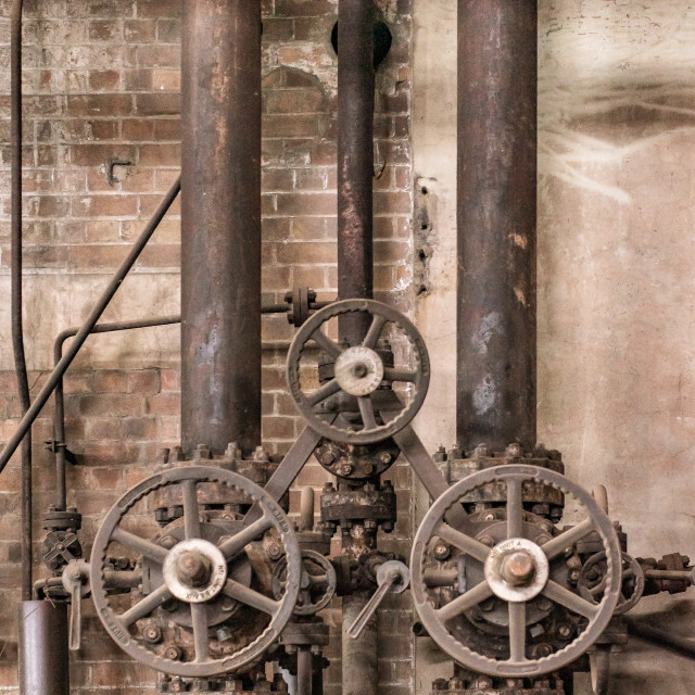 """Pipes and valves in an abandoned industrial factory with a vintage feel"" stock image"