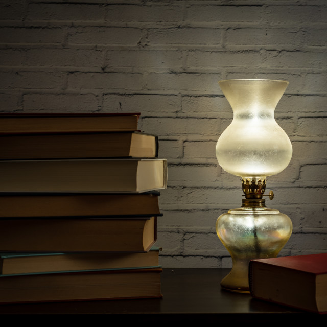 """""""The light of an oil lamp illuminates books placed on a dark wood"""" stock image"""