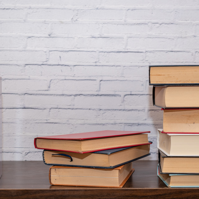 """""""A few books of various sizes arranged on a dark wooden shelf"""" stock image"""