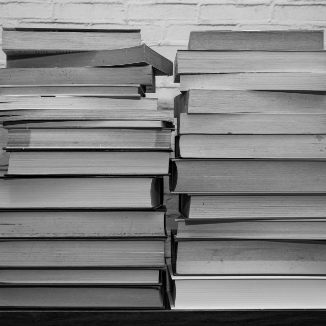 """""""Black and white image of some books stacked on a shelf"""" stock image"""